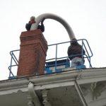 Workers installing chimney liner